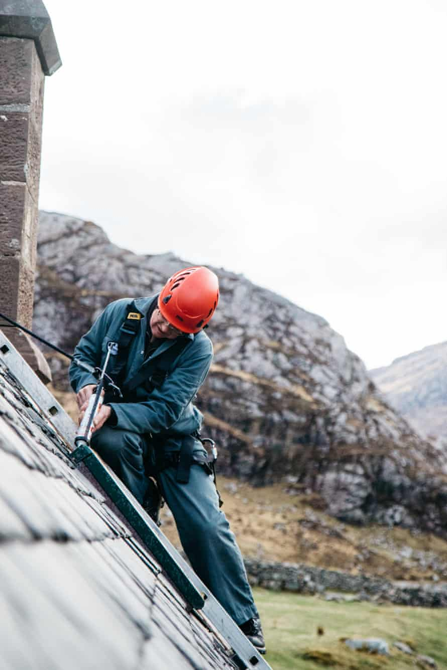 Robbie, a bothy volunteer, in hard hat and overalls, repairs a bothy roof.