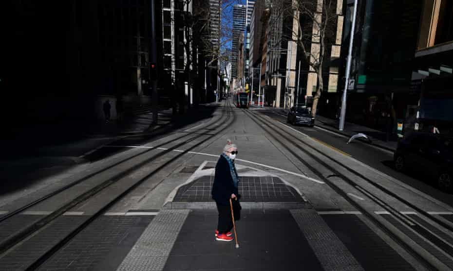 A woman using a walking stick crosses a deserted street in Sydney's CBD