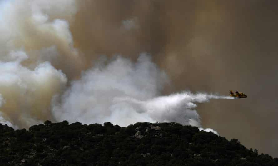 A plane drops water over a wildfire on the edge of Cenicientos, central Spain, in June.
