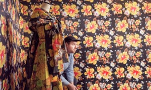 Richard Quinn in his studio surrounded by a bold yellow, orange and brown floral print and with a dummy draped in the same material