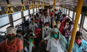 Indian migrant laborers ride in the bus organised by Brihanmumbai Municipal Corporation for the Lokmanya Tilak Terminus to catch the train for Patna, to reach their villages. Photo credit: EPA/DIVYAKANT SOLANKI