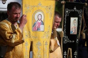 Orthodox altar servers carry gonfalons