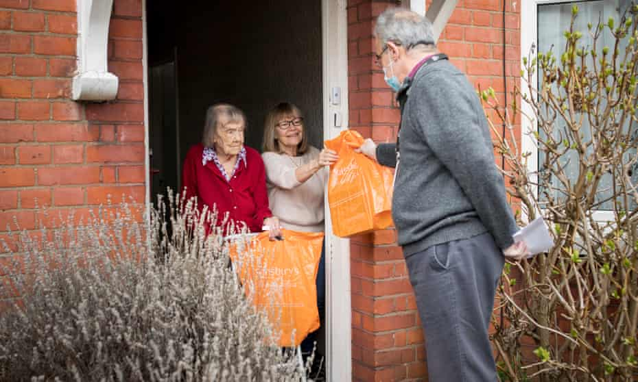 Rob Costa, 62, delivering audio books to Mabel, 104 and her daughter Chris, 67 in north London