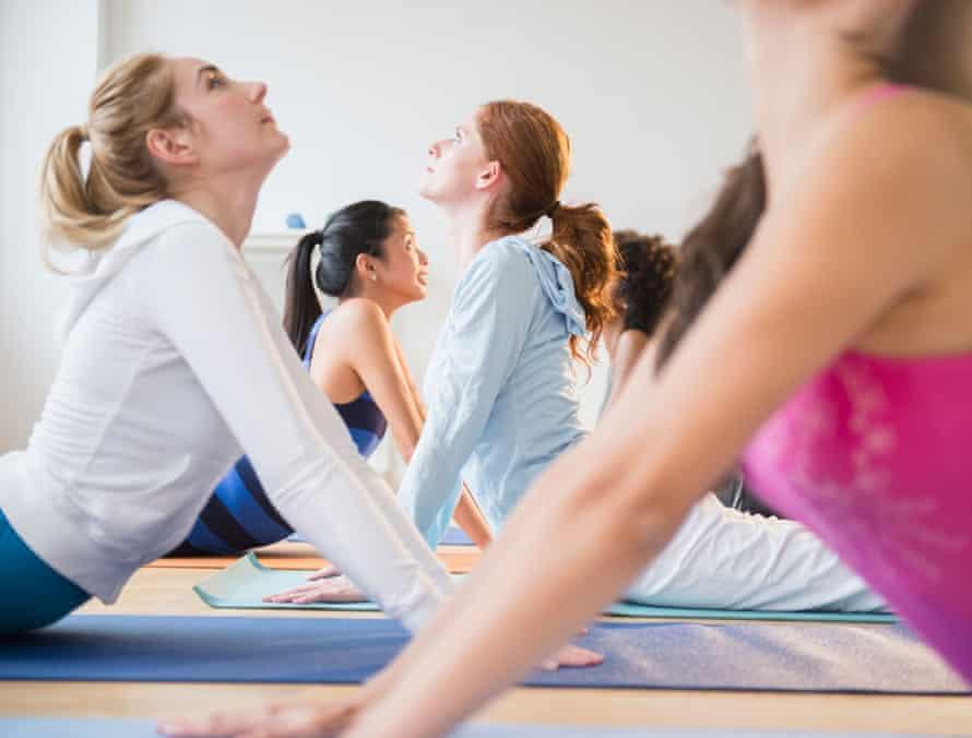 Women practise yoga in class.
