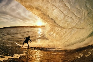 A surfer pulls out of a barrel at sunset