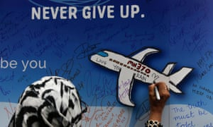 a woman writes a message on a board for victims of mh370