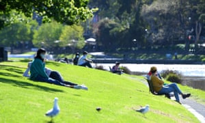 People are seen enjoying the sun along the Yarra river in Melbourne.