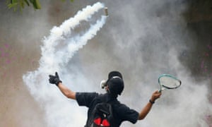 A demonstrator uses a racket against a tear gas canister during a protest for the government's handling of the pandemic in Bangkok, Thailand.