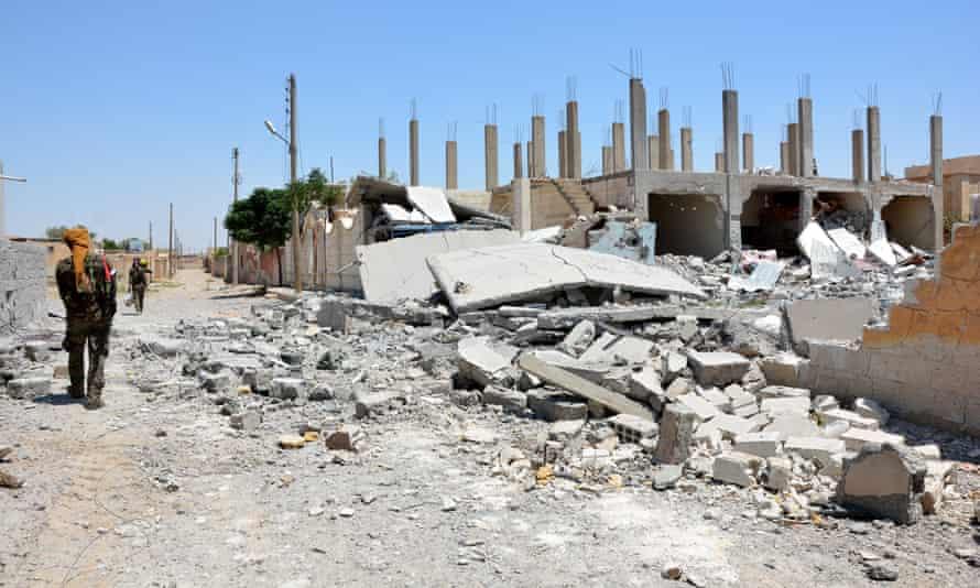 Men patrol next to destroyed buildings at Raqqa on 11 June.