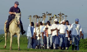 A corrections officer on horseback watches a work crew head to the fields of the prison farm at the Louisiana State Penitentiary in Angola, La. Louisiana is among at least 14 states that receive subsidies on crops grown by convicts on prison farms. At least $17 million in crop subsidies went to government agencies including airports, wildlife departments and prisons.