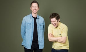 John Robins, standing, wearing a blue denim shirt and Elis James, standing next to him and bent over laughing, in a yellow polo shirt