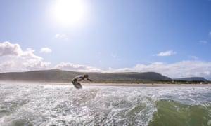 A surfer heads in to Benone beach, Northern Ireland.