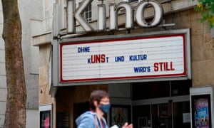 A woman passes by a closed cinema with a board displaying 'Without art and culture it's getting quiet' in Stuttgart, Germany.