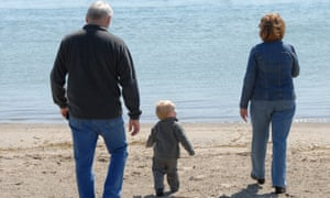 Grandparents with their grandson on a beach