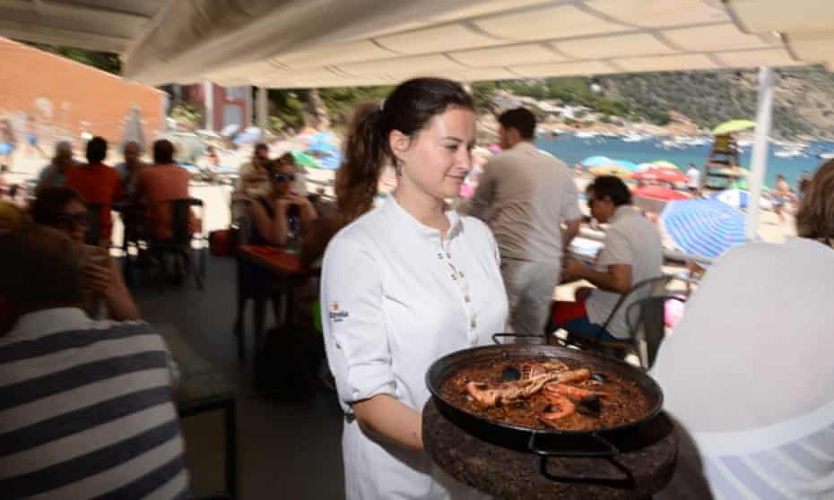 Waitress about to serve a dish of seafood to diners on the terrace at Toc Al Mar, Begur, Catalonia