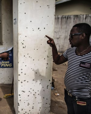 A man points out bullet holes at the headquarters of Jean Ping, Gabon's opposition leader.