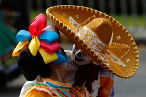 """A couple dressed up as a """"Catrina and Catrin"""", a Mexican character also known as """"The Elegant Death"""", kisses as they participate in a procession to commemorate Day of the Dead in Mexico City"""