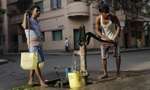 Men get water from a roadside pump in Kolkata, India