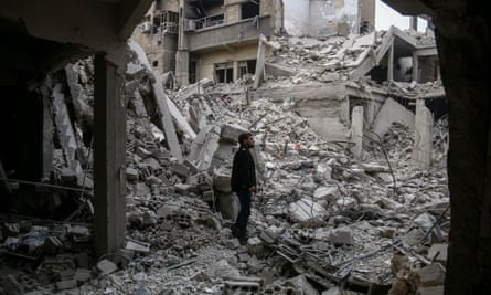 A man stands amid the wreckage after a regime strike in Arbin, eastern Ghouta, Syria.