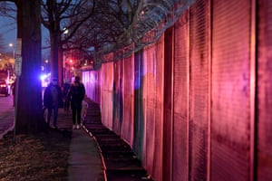 Pedestrians walk next to the razor-topped fence around the Capitol building