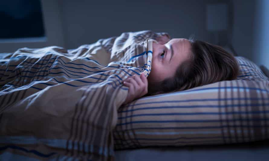 Woman looking scared under a blanket in bed
