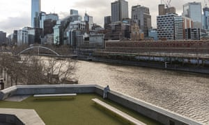 A man looks out towards the Yarra River and the Melbourne CBD during lockdown