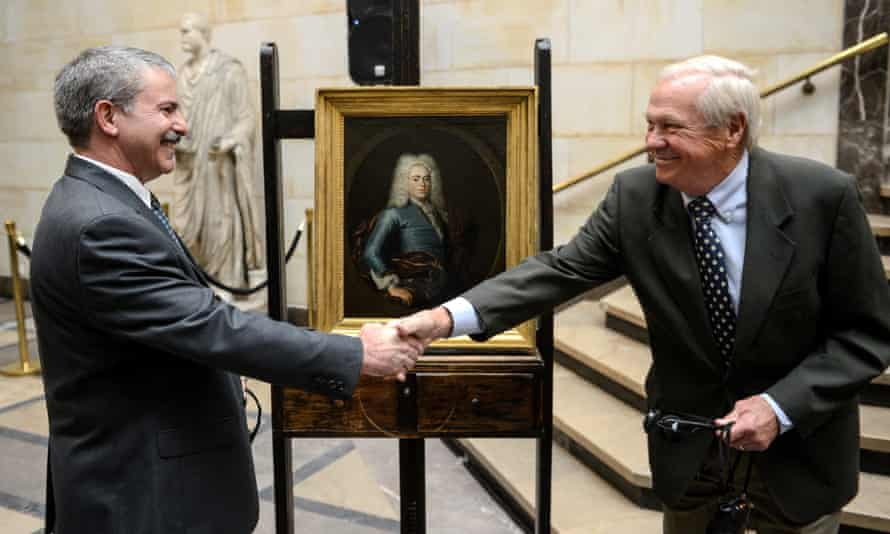 John Bobb, right, shakes hands with Bob Wittmann during a press conference at the National Museum in Warsaw.