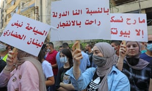 Demonstrators lift placards during a rally called for by the Lebanese Federation for Tourism Industries in downtown Beirut to protest the government's lack of support for the sector and its workforce, in the aftermath of the monster explosion which ravaged the city in early August.