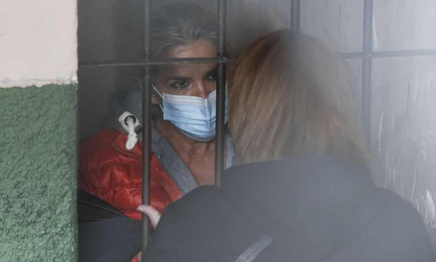 Standing behind bars, Bolivia's former interim president Jeanine Anez speaks to an unidentified woman at a police station in La Paz.