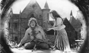 Lon Chaney as Quasimodo chained to a stone wheel and Patsy Ruth Miller as Esmeralda in the 1923 film The Hunchback of Notre Dame.