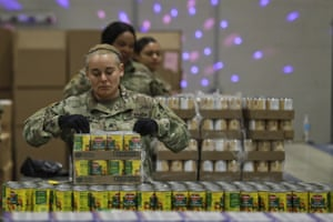 "Ohio National Gaurd Sgt. Kelley Kremer assists in repackaging emergency food boxes for food distribution at the Cleveland Food Bank, Tuesday, March 24, 2020, in Cleveland. State parks have shuttered cabins, golf courses and marinas as Ohio enters its first full day of a statewide ""stay at home"" order to slow the spread of the coronavirus. Grocery stores, gas stations and other essential businesses remain open."