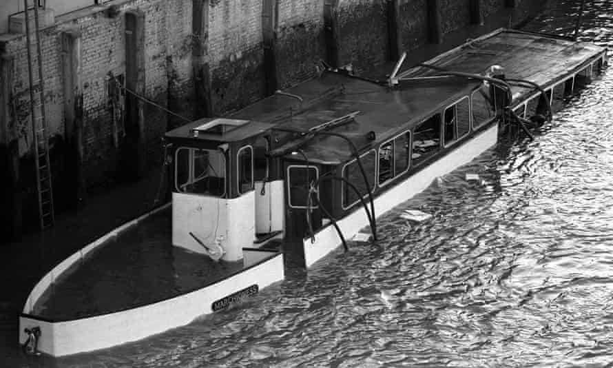 The wrecked hull of the Marchioness lying partially submerged in shallow water after it was hit by a dredger, Bowbelle, in August 1989.