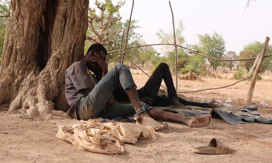 A teenager shackled beneath a tree in Poessen in Burkina Faso after been seized by members of a local branch of the Koglweogo.