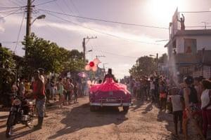 A girl rides around her neighbourhood in a pink 1950s convertible