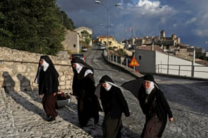 Nuns walk up to the entrance of a church in nearby Castel del Monte