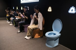 Visitors pretend to give a push while sitting on colourful toilet bowls