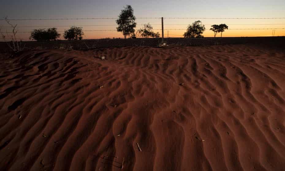 A mini sand dune along a fenceline