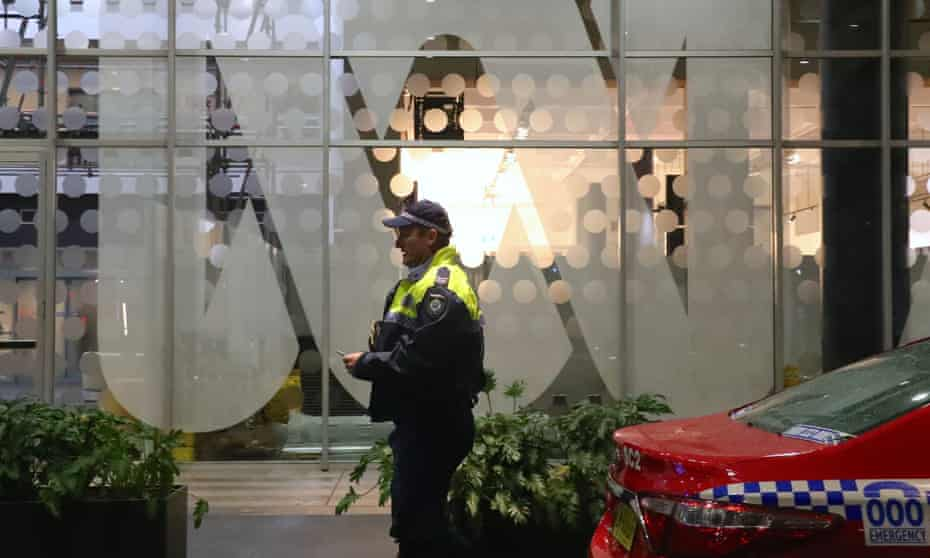 A police officer walks past the ABC logo at the main entrance to the ABC building in Ultimo, Sydney in June