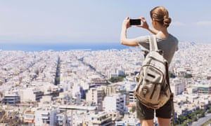 Young woman taking a picture over a city with her mobile phone