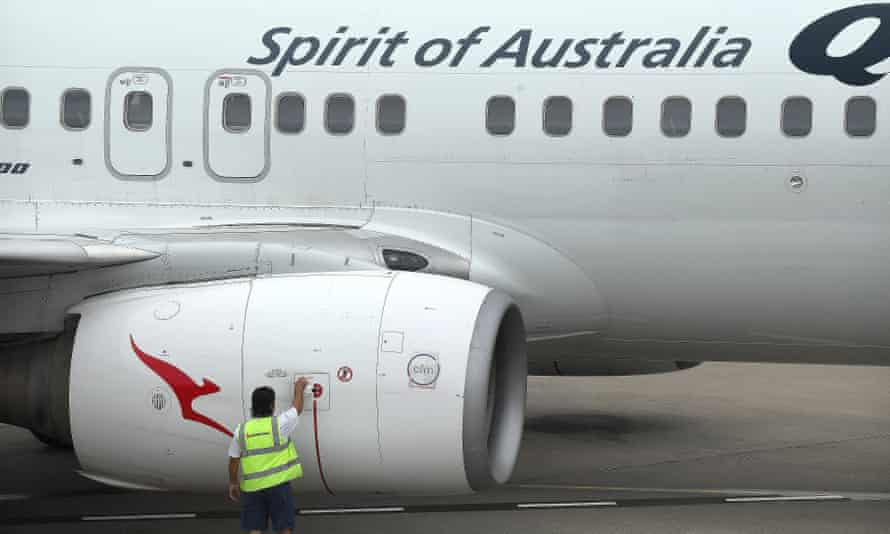 A ground crew member attends to the engine of a Qantas aircraft in Brisbane