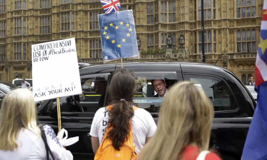 A man in a passing taxi shouts his disagreement at anti-Brexit protesters near the Houses of Parliament in London.