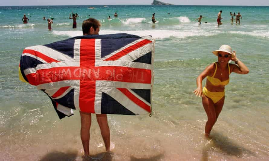 Tourists holding union jack on the beach at Benidorm, Spain.
