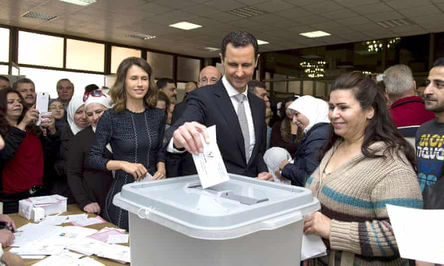 Syrian president, Bashar al-Assad casts his vote next to his wife Asma (left) at a polling station in Damascus.