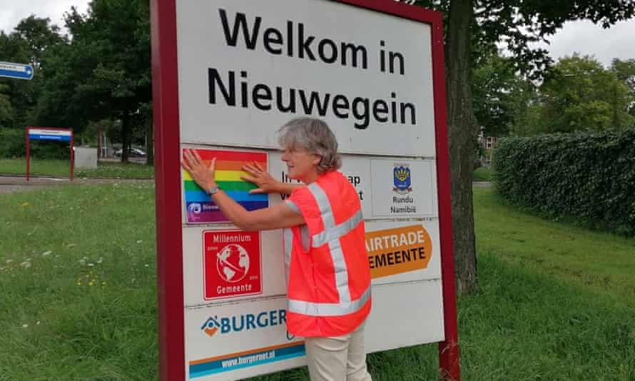 Marieke Schouten, a councillor in Nieuwegein, sticks a rainbow flag over the Puławy name on a sign outside the Dutch town.