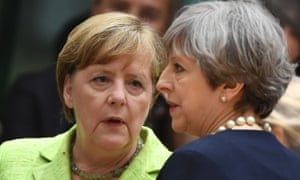 German Chancellor Angela Merkel (L) and British Prime Minister Theresa May talk as they attend an European Union leaders summit.