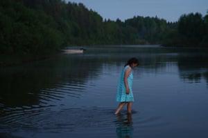 A pilgrim takes a dip in the Velikaya River