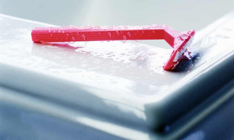 Pink razor on the rim of a bath