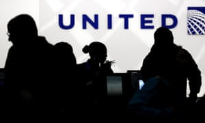 Passengers seen in silhouette at a United Airlines check-in desk.