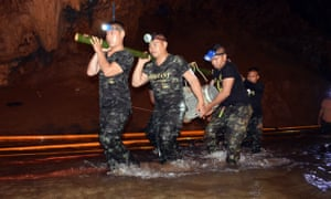 Thai soldiers carry equipment inside the flooded cave complex