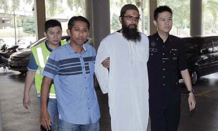 Salah Salem Saleh Sulaiman, a Danish national, is escorted by police to a court in Kuala Lumpur.
